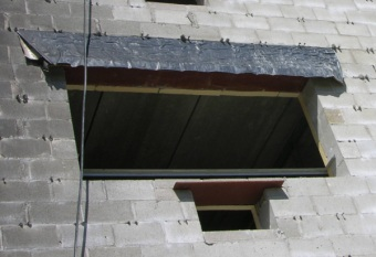 This mason knows what he is doing. Through-wall flashing in block backup wall is a few courses above the lintel location. Tiebacks are seen dotting the face of the block.
